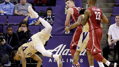 Washington's Markelle Fultz, left, flips after chasing a ball against Washington State in the first half of an NCAA college basketball game Sunday, Jan. 1, 2017, in Seattle. (AP Photo/Elaine Thompson)