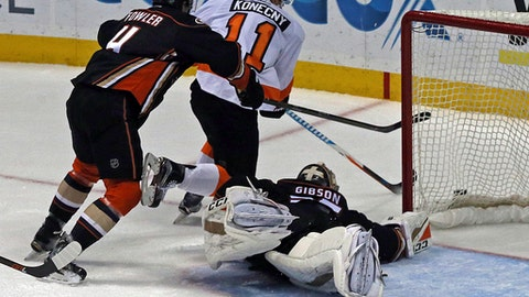 Anaheim Ducks goalie John Gibson (36) hits the ice to block the puck, as defenseman Cam Fowler and Philadelphia Flyers center Travis Konecny (11) go after it during the second period of an NHL hockey game in Anaheim, Calif., Sunday, Jan. 1, 2017. (AP Photo/Reed Saxon)
