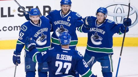 Vancouver Canucks' Sven Baertschi, from top left, Henrik Sedin, of Sweden, Troy Stecher and Daniel Sedin, bottom, of Sweden, celebrate Baertschi's second goal against the Colorado Avalanche during the third period of an NHL hockey game in Vancouver, British Columbia, Monday, Jan. 2, 2017. Baertschi scored twice, including the winner on a power play with under four minutes to go in the third period. Vancouver won, 3-2. (Darryl Dyck/The Canadian Press via AP)