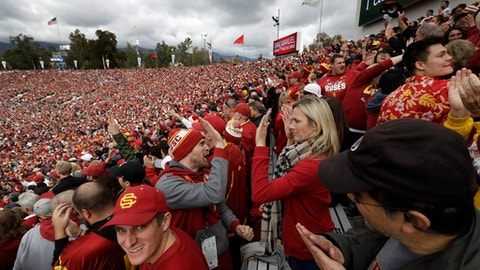 FILE - In this Monday, Jan. 2, 2017, file photo, Southern California high-five for their team during the first half of the Rose Bowl NCAA college football game in Pasadena, Calif. Too many bowls. Made-for-TV bowls. The College Football Playoff has changed the postseason, or at least how some people feel about it. More and more the question is asked: What should the bowls be? (AP Photo/Richard Vogel, File)