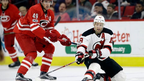 Carolina Hurricanes' Victor Rask (49), of Sweden, and New Jersey Devils' Travis Zajac (19) chase the puck during the second period of an NHL hockey game in Raleigh, N.C., Tuesday, Jan. 3, 2017. (AP Photo/Gerry Broome)