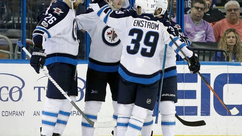 Winnipeg Jets defenseman Jacob Trouba, second from left, celebrates his goal against the Tampa Bay Lightning with teammates Blake Wheeler, and defenseman Toby Enstrom (39), of Sweden, during the second period of an NHL hockey game Tuesday, Jan. 3, 2017, in Tampa, Fla. (AP Photo/Chris O'Meara)
