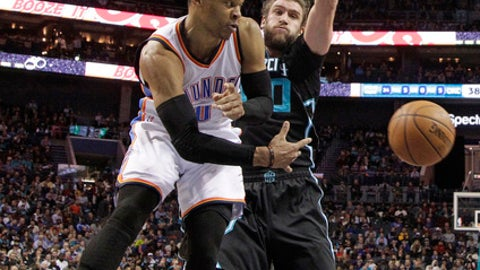 Oklahoma City Thunder's Russell Westbrook, front, passes the ball as Charlotte Hornets' Spencer Hawes, back, defends in the first half of an NBA basketball game in Charlotte, N.C., Wednesday, Jan. 4, 2017. (AP Photo/Chuck Burton)