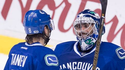 Vancouver Canucks goalie Ryan Miller (30) celebrates his shutout against the Arizona Coyotes with teammate Christopher Tanev (8) during the third period of an NHL hockey game, Wednesday, Jan. 4, 2017, in Vancouver, British Columbia.  (Jonathan Hayward/The Canadian Press via AP)