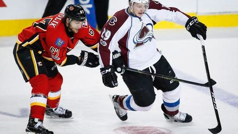Colorado Avalanche's Nathan MacKinnon, right, gets away from Calgary Flames' Michael Frolik, from the Czech Republic, during the third period of an NHL hockey game, Wednesday, Jan. 4, 2017, in Calgary, Alberta.  (Jeff McIntosh/The Canadian Press via AP)