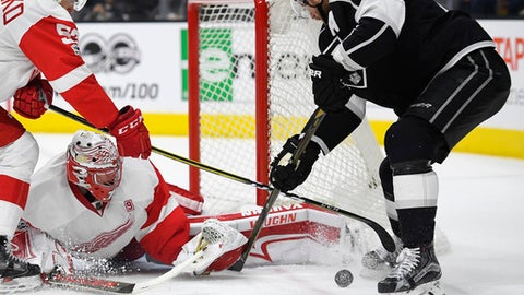 Los Angeles Kings center Jeff Carter, right, tries to get a shot past Detroit Red Wings defenseman Alexey Marchenko, left, of Russia, and goalie Jared Coreau during the second period of an NHL hockey game, Thursday, Jan. 5, 2017, in Los Angeles. (AP Photo/Mark J. Terrill)