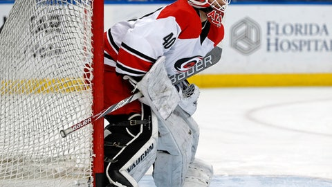 FILE - In this Dec. 31, 2016, file photo, Carolina Hurricanes equipment manager Jorge Alves warms up after signing a contract to dress as an emergency backup for the NHL hockey team's game against the Tampa Bay Lightning, in Tampa, Fla. Hockey is the only professional sport where someone can go from being a fan to suiting up in the NHL. Injuries and illnesses to goaltenders have opened the door for anyone from equipment managers to Zamboni drivers and amateur coaches to dress or even play goal in an NHL game. (AP Photo/Mike Carlson, File)