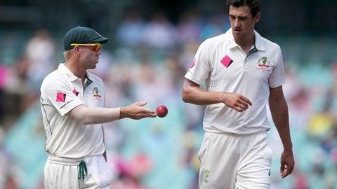 Australia's David Warner, left, tosses the ball to teammate Mitchell Starc during their cricket test match against Pakistan in Sydney, Australia, Saturday, Jan. 7, 2017. (AP Photo/Rick Rycroft)