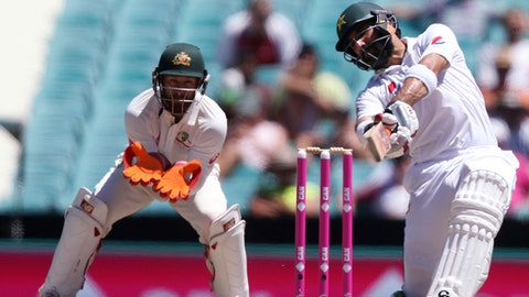 Pakistan's Misbah-ul-Haq, right, drives the ball against Australia during their cricket test match in Sydney, Australia, Saturday, Jan. 7, 2017. (AP Photo/Rick Rycroft)