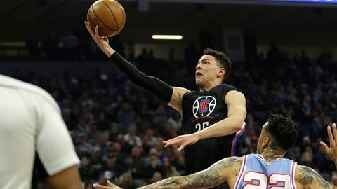 LA Clippers guard Austin Rivers, center, drives to the basket against Sacramento Kings forward Matt Barnes during the first half of an NBA basketball game Friday, Jan. 6, 2017, in Sacramento, Calif. (AP Photo/Rich Pedroncelli)