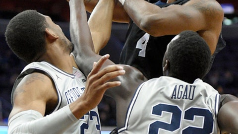 Butler forward Tyler Wideman (4) is fouled by Georgetown guard Rodney Pryor (23) during the first half of an NCAA college basketball game, Saturday, Jan. 7, 2017, in Washington. Georgetown forward Akoy Agau (22) reaches in on the play. (AP Photo/Nick Wass)