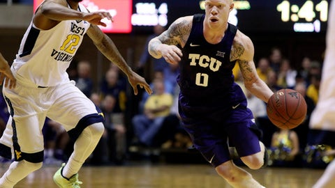 TCU guard Jaylen Fisher (0) drives to the basket as West Virginia guard Tarik Phillip (12) defends during the first half of an NCAA college basketball game, Saturday, Jan. 7, 2017, in Morgantown, W.Va. (AP Photo/Raymond Thompson)