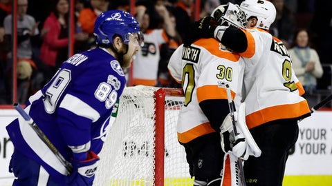 Philadelphia Flyers' Ivan Provorov (9) and Michal Neuvirth (30) celebrate their 4-2 win as as Tampa Bay Lightning's Nikita Nesterov (89) skates past after an NHL hockey game, Saturday, Jan. 7, 2017, in Philadelphia. (AP Photo/Matt Slocum)