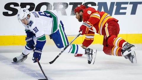 Vancouver Canucks' Markus Granlund, left, of Finland, dodges a check from Calgary Flames' Dennis Wideman during third-period NHL hockey game action in Calgary, Alberta, Saturday, Jan. 7, 2017. (Jeff McIntosh/The Canadian Press via AP)