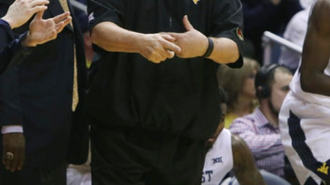 West Virginia head coach Bob Huggins mimics a traveling signal to a referee during the first half of an NCAA college basketball game against Baylor, Tuesday, Jan. 10, 2017, in Morgantown, W.Va. (AP Photo/Raymond Thompson)