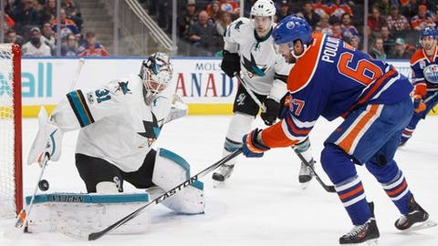 San Jose Sharks' goalie Martin Jones (31) makes a save on Edmonton Oilers' Benoit Pouliot (67) during the second period of an NHL hockey game, Tuesday, Jan. 10, 2017 in Edmonton, Alberta.  (Jason Franson/The Canadian Press via AP)