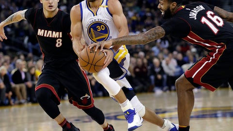 Golden State Warriors' Stephen Curry (30) drives between Miami Heat's Tyler Johnson (8) and James Johnson (16) during the second half of an NBA basketball game Tuesday, Jan. 10, 2017, in Oakland, Calif. Golden State won 107-95. (AP Photo/Marcio Jose Sanchez)