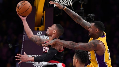 Portland Trail Blazers guard Damian Lillard, left, shoots as Los Angeles Lakers center Tarik Blackdefends  during the second half of an NBA basketball game, Tuesday, Jan. 10, 2017, in Los Angeles. The Trail Blazers won 108-87. (AP Photo/Mark J. Terrill)