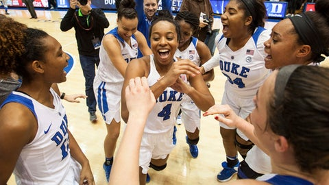 FILE - In this Dec. 4, 2016, file photo, Duke's Lexie Brown (4) celebrates with her teammates following a victory in an NCAA college basketball game against South Carolina, in Durham, N.C. Lexie Brown's father is best known for his creative dunks. The daughter of Dee Brown is drawing attention for making a more mundane shot with uncommon consistency. The versatile Duke guard has made a school-record 53 consecutive free throws, and her poise is one reason the 12th-ranked Blue Devils are back among the top teams in women's basketball after a one-year blip. (AP Photo/Ben McKeown, File)