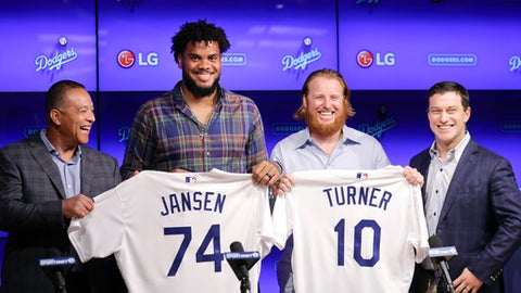 Los Angeles Dodgers closer Kenley Jansen and third baseman Justin Turner pose for photos with manager Dave Roberts, left, and Andrew Friedman, president of baseball operations, right, following a news conference Wednesday, Jan. 11, 2017, in Los Angeles. The two re-signed with the team as free agents. (AP Photo/Jae C. Hong)