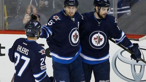 Winnipeg Jets' Nikolaj Ehlers (27), Mark Scheifele (55) and Drew Stafford (12) celebrate after Scheifele's goal against the Montreal Canadiens during the first period of an NHL hockey game, Wednesday, Jan. 11, 2017 in Winnipeg, Ontario.  (John Woods/The Canadian Press via AP)