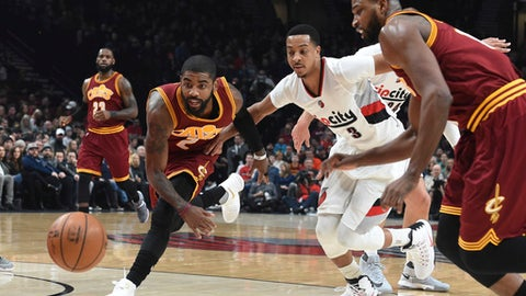 Cleveland Cavaliers guard Kyrie Irving goes after a loose ball with Portland Trail Blazers guard C.J. McCollum during the first half of an NBA basketball game in Portland, Ore., Wednesday, Jan. 11, 2017. (AP Photo/Steve Dykes)