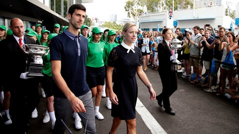 Defending men's and woman's champions Serbia's Novak Djokovic, left, and Germany's Angelique Kerber walk past fans to the official draw ceremony ahead of the Australian Open tennis championships in Melbourne, Australia, Friday, Jan. 13, 2017. (AP Photo/Mark Baker)