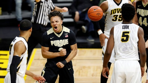 Purdue guard Carsen Edwards, center, reacts between Iowa's Christian Williams, left, and Tyler Cook (5) after making a basket during the first half of an NCAA college basketball game, Thursday, Jan. 12, 2017, in Iowa City, Iowa. (AP Photo/Charlie Neibergall)
