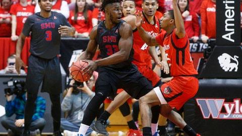 SMU's Semi Ojeleye (33) looks to pass against Cincinnati's Kevin Johnson, right, in the first half of an NCAA college basketball game, Thursday, Jan. 12, 2017, in Cincinnati. (AP Photo/John Minchillo)
