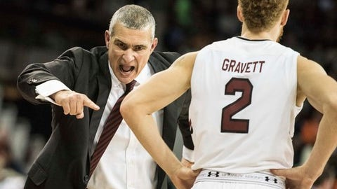 In this Wednesday, Dec. 21, 2016, photo, South Carolina head coach Frank Martin communicates with South Carolina guard Hassani Gravett (2) during the second half of an NCAA college basketball game in Columbia, S.C. Martin was once a bouncer in Miami and, at times, looks as if he's about to charge onto the court to take down an offending official or player. (AP Photo/Sean Rayford)