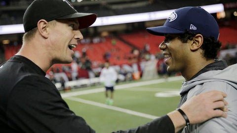Atlanta Falcons quarterback Matt Ryan, left, speaks with Seattle Seahawks quarterback Russell Wilson before the first half of an NFL football NFC divisional playoff game, Saturday, Jan. 14, 2017, in Atlanta. (AP Photo/David Goldman)