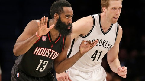 Houston Rockets' James Harden, left, reacts after making a basket while Brooklyn Nets' Justin Hamilton runs alongside him during the second half of the NBA basketball game at the Barclays Center, Sunday, Jan. 15, 2017 in New York. The Rockets defeated the Nets 137-112. (AP Photo/Seth Wenig)
