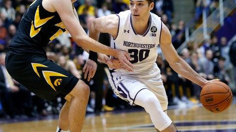 Northwestern guard Bryant McIntosh, right, drives against Iowa forward Nicholas Baer during the second half of an NCAA college basketball game Sunday, Jan. 15, 2017, in Evanston, Ill. Northwestern won 89-54. (AP Photo/Nam Y. Huh)