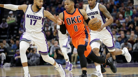 Oklahoma City Thunder guard Russell Westbrook, center, races down court against Sacramento Kings' Garrett Temple, left, and Rudy Gay during the first half of an NBA basketball game Sunday, Jan. 15, 2017, in Sacramento, Calif. (AP Photo/Rich Pedroncelli)