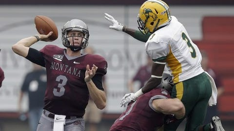 FILE - In this Aug. 29, 2015 file photo, Montana's quarterback Brady Gustafson (3) passes the ball as North Dakota State's Tre Dempsey (3) defends during an NCAA college football game in Missoula, Mont. Montana rallied to win the game 38-35 on the final play of the game. NDSU's quest for a fifth straight Football Championship Subdivision title continues at home in Fargo on Saturday, Dec. 5, 2015, when they host Montana in a game for a chance to make up for the season-opening setback. (AP Photo/Rick Bowmer, File)