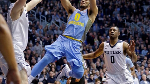 Marquette guard Markus Howard (0) shoots between Butler forward Andrew Chrabascz (45) and guard Avery Woodson (0) in the second half of an NCAA college basketball game in Indianapolis, Monday, Jan. 16, 2017. Butler defeated Marquette 88-80. (AP Photo/Michael Conroy)