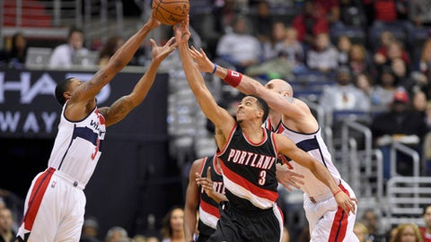 Washington Wizards guard Bradley Beal, right, and center Marcin Gortat, left, of Poland, battle for the ball against Portland Trail Blazers guard C.J. McCollum, center, during the first half of an NBA basketball game, Monday, Jan. 16, 2017, in Washington. (AP Photo/Nick Wass)