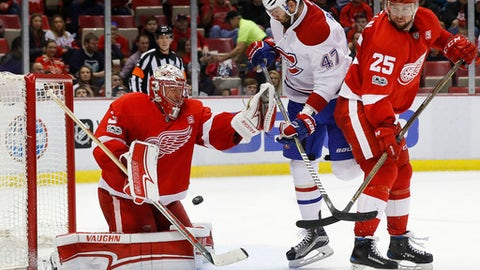 Detroit Red Wings goalie Jared Coreau (31) stops a Montreal Canadiens shot as Montreal Canadiens right wing Alexander Radulov (47) and defenseman Mike Green (25) battle for position in the third period of an NHL hockey game, Monday, Jan. 16, 2017, in Detroit. (AP Photo/Paul Sancya)