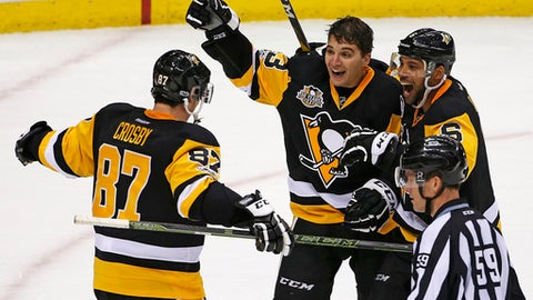 Pittsburgh Penguins' Conor Sheary, center, celebrates his game-winning overtime goal with Sidney Crosby (87) and Trevor Daley (6) at the end of an NHL hockey game against the Washington Capitals in Pittsburgh, Monday, Jan. 16, 2017. The Penguins won 8-7. (AP Photo/Gene J. Puskar)