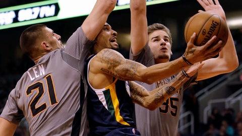 Utah Jazz guard George Hill drives between Phoenix Suns center Alex Len (21) and Dragan Bender in the third quarter during an NBA basketball game, Monday, Jan. 16, 2017, in Phoenix. (AP Photo/Rick Scuteri)