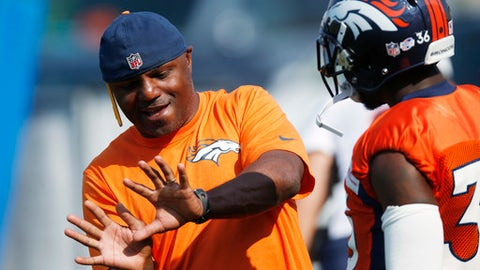 Denver Broncos defensive backs coach Joe Woods, left, gestures while speaking to cornerback Kayvon Webster during the team's NFL football training camp session early Thursday, Aug. 20, 2015, in Englewood, Colo. (AP Photo/David Zalubowski)