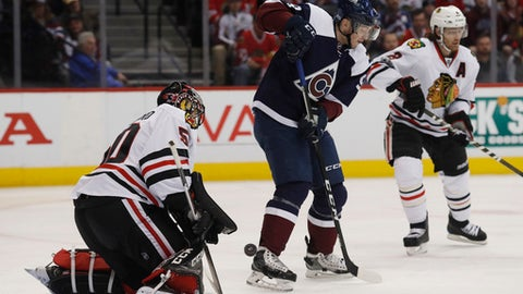 Colorado Avalanche center Matt Duchene, center, redirected the puck at Chicago Blackhawks goalie Corey Crawford, left, as defenseman Duncan Keith covers in the first period of an NHL hockey game, Tuesday, Jan. 17, 2017, in Denver. (AP Photo/David Zalubowski)