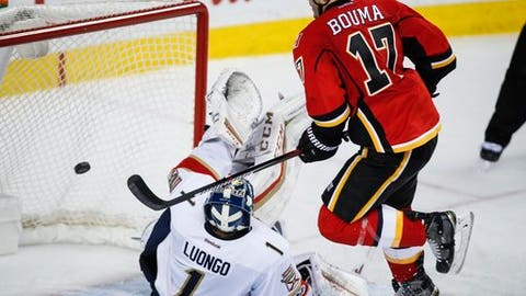 Florida Panthers goalie Roberto Luongo, left, tries to stop a goal from Calgary Flames' Lance Bouma during third period NHL hockey action in Calgary, Tuesday, Jan. 17, 2017. (Jeff McIntosh/The Canadian Press via AP)