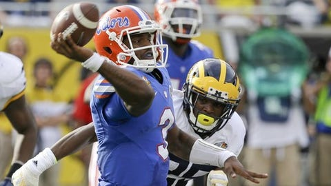 Florida quarterback Treon Harris, left, throws a pass as Michigan safety Dymonte Thomas chases him during the second half of the Citrus Bowl NCAA college football game, Friday, Jan. 1, 2016, in Orlando, Fla.  Michigan won 41-7. (AP Photo/John Raoux)
