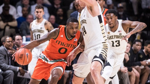 Miami guard Ja'Quan Newton (0) dribbles into defense from Wake Forest forward Dinos Mitoglou (44)  during an NCAA college basketball game Wednesday, Jan. 18, 2017, in Winston-Salem, N.C. (Andrew Dye/The Winston-Salem Journal via AP)