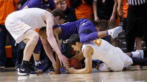 Kansas State forward Wesley Iwundu, center, falls over Oklahoma State guard Lindy Waters III, right, as they and Oklahoma State forward Mitchell Solomon. left, reach for the ball during the second half of an NCAA college basketball game in Stillwater, Okla., Wednesday, Jan. 18, 2017. Kansas St won 96-88. (AP Photo/Sue Ogrocki)