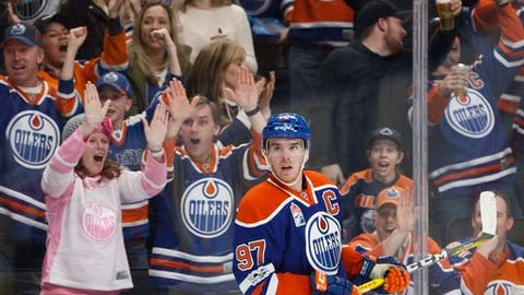Fans celebrate an overtime goal by Edmonton Oilers' Connor McDavid (97) against the Florida Panthers during an NHL hockey game Wednesday, Jan. 18, 2017, in Edmonton, Alberta. (Jason Franson/The Canadian Press via AP)