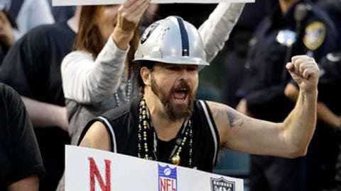FILE - In this Nov. 6, 2016, file photo, Oakland Raiders fans hold up signs about the team's possible move to Las Vegas during an NFL football game between the Raiders and Denver Broncos in Oakland, Calif. The Oakland Raiders have filed paperwork to move to Las Vegas. Clark County Commission Chairman Steve Sisolak told The Associated Press on Thursday, Jan. 19, 2017, that he spoke with the Raiders. (AP Photo/Marcio Jose Sanchez, File)