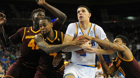 UCLA guard Lonzo Ball is fouled while driving against Arizona State's Jethro Tshisumpa, Torian Graham and Tra Holder, from left, during the second half of an NCAA college basketball game in Los Angeles, Thursday, Jan. 19, 2017. UCLA beat Arizona State 102-80. (AP Photo/Michael Owen Baker)