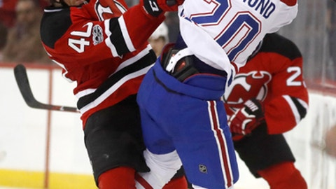 New Jersey Devils center Blake Coleman, left, hits Montreal Canadiens defenseman Zach Redmond during the second period of an NHL hockey game, Friday, Jan. 20, 2017, in Newark, N.J. (AP Photo/Julio Cortez)